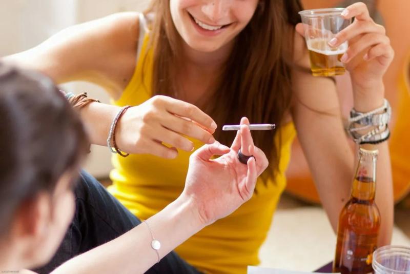 Девушка со стаканом берет сигарету